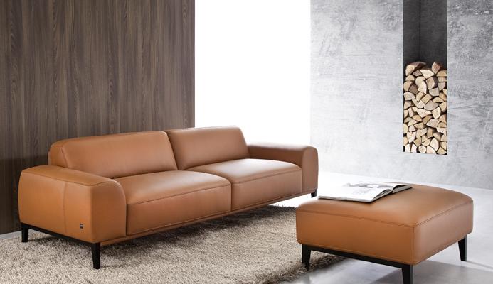 Pohovka a taburet POINT s jednoduchými čistými tvarmi v hnedej koži.