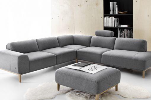 Moderná sedačka a taburet POINT s jednoduchými čistými tvarmi v šedej látke.