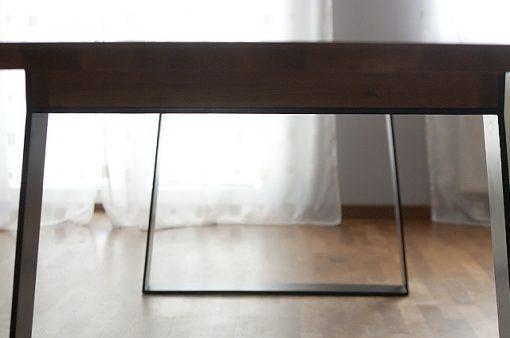 Detail na bok stola HOLAN s kovovými nohami.