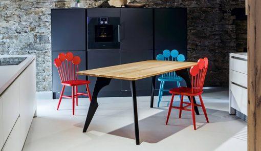 Tri dizajnové stoličky PAF v modrej a červenej farbe v interiéri kuchyne.