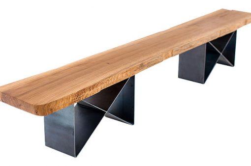 Hrubý, monoliticky pôsobiaci stolový plát v kombinácii s nápaditou podnožou lavice NATURIST dodáva interiéru ráz majestátnosti a luxusu.